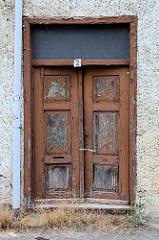 Alte Holztür / Doppeltür mit abgeblätterter Farbe -  Wohnhaus mit Rauhputz in der Hansestadt Havelberg.