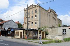 Kleine Geschäftshäuser  in der Hauptstraße Tadeusza Kościuszki von Pieszyce / Peterswaldau. Dahinter die Industriearchitektur eines leerstehendes Fabrikgebäudes.