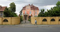 Aufwendig restaurierte historische Villa im Baustil des Historismus, die Fassade ist in kräftigen rosa gestrichen. An der Straße grenzt eine gelbe Ziegelmauer mit aufwändige schmiedeeisernen Tor das Grundstück ab.