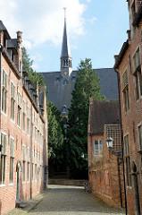 Blick durch die  Bovenstraat beim Großen Beginenhof  zur Sint Jan de Doper /  St. Johannes der Täufer) Basiklik  in Löwen / Leuven. Der Löwener Beginenhof ist ein typischer Stadtbeginenhof mit zahlreichen kleinen Straßen und Plätzen.
