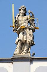 Skulptur Justitia mit vergoldetem Schwert und goldener Waage auf dem Gesims des historischen Rathauses von Budweis /  České Budějovice. Das Bauwerk im Stil des Barock wurde 1730 nach den Plänen des Architekten Anton Erhard Martinelli errichtet.