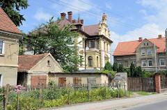 Wohnhäuser im unterschiedlichen Baustil in der Straße Tadeusza Kościuszki von Pieszyce / Peterswaldau. Mehrstöckiges Gebäude mit grauer Putzfassade sowie eine Villa in gründerzeitlicher Schmuckarchitektur.