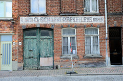 Fassade eines alten Gewerbegebäudes mit Holztor und kaum lesbarer Fassadenaufschrift in der Peterseliestraat von Brügge.