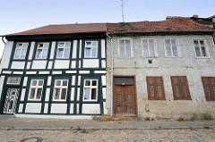 Alt + Neu; restauriertes Wohnhaus mit grün gestrichenem Fachwerk; daneben ein leerstehendes Wohnhaus mit Rauhputz und Fensterluken.
