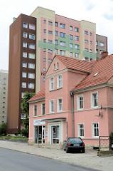Einzelhaus in der Straße Wolności in Langenbielau/ Bielawa, dahinter ein Hochhaus mit farblich abgesetzter Fassade.