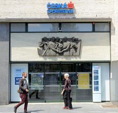 Moderner Eingang einer Bank in Budweis /  České Budějovice, darüber ein Relief mit sozialistischem Kunstverständnis-Darstellung der emsig arbeitenden, sparsamen Arbeiterklasse.