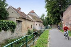 Wohnhäuser und schmale Straße entlang vom Bach Kamionka in Pieszyce / Peterswaldau.