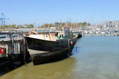 Alter Fischereihafen  in Seebrügge, ein Fischerboot liegt am Steg, dahinter der Sportboothafen / Marina.