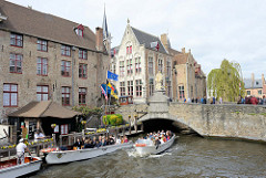 Touristenboote in der historischen Innenstadt von Brügge - flache Boote, da niedrige Brückendurchfahrt.
