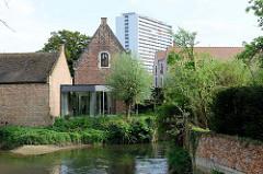 Blick über den  Fluss Dijle zu Gebäuden vom Großen Beginenhof  in Löwen / Leuven. Der Löwener Beginenhof ist ein typischer Stadtbeginenhof mit zahlreichen kleinen Straßen und Plätzen.