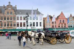 Großer Markt / Marktplatz   im historischen Zentrum der Stadt Brügge - alte flämische Architektur als Randbebauung, Pferdedroschken warten auf Touristen.