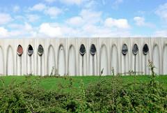 Fassade einer Betonhalle mit tropfenförmigen Fenstern am Steenkaai, Gent-Oostende-Kanal bei Brügge - Lagerhalle.
