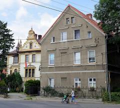 Wohnhäuser im unterschiedlichen Baustil in der Straße Tadeusza Kościuszki von Pieszyce / Peterswaldau. Mehrstöckiges Gebäude mit grauer Putzfassade, dahinter eine Villa in gründerzeitlicher Schmuckarchitektur.