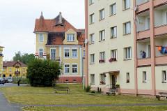 Fassade eines schlichten  Hochhauses vor einer Gründerzeitvilla mit rundem Eckturm und ziegelgedeckten Dach in Franzensbad - Františkovy Lázně.