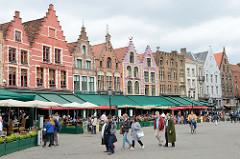 Historische flämische Architektur mit Treppengiebeln als Randbebauung am Groten Markt in Brügge.  Straßen- Cafés und Restaurants laden die Touristen zum Verweilen ein, heruntergelassen Markisen schützen vor der Sonne.