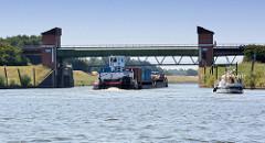 Mündung / Einfahrt zum Elbe Seitenkanal an der Elbe bei   Artlenburg . Ein Binnenschiff und ein Sportboot fahren in den Kanal ein.