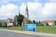 Blaues Wartehäuschen einer Bushaltestelle an einer Wiese, dahinter die St.-Antonius-Kirche von Peterswaldau / Pieszyce, erbaut 1875.