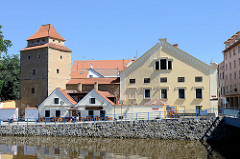 """Blick über den Fluss Maltsch / Malše zur historischen Innenstadt von Budweis / České Budějovice. Links der Festungsturm Eiserne Jungfrau; Teil der gotischen Stadtbefestigung - in der Wehranlage befand sich die Folterkammer der Stadt, die """"Eiserne Jun"""