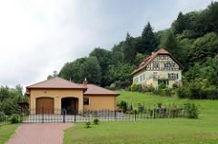 Wohnhäuser am Eulengebirge in  Pieszyce / Peterswaldau;  Flachbau eines Bungalows mit Garagen und mit Metallzaun eingegrenztes Grundstück, dahinter eine Villa mit Fachwerkgiebel zwischen Bäumen am Berghang.