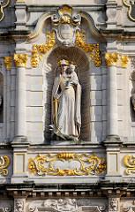 Detail  der Universitätsbibliothek in der Stadt Löwen/Leuven; wehrhafte Maria mit vergoldeten Schwert die einen Greif / Drachen zu ihren Füßen bezwungen hat, dabei hält sie das Christkind auf dem Arm.