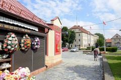 Geschäft mit Plastikblumen, Kränzen aus Plastik, im Hintergrund das Verwaltungsgebäude der Bezirksverwaltung von   Pieszyce / Peterswaldau.