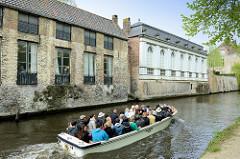Ein mit Touristen vollbesetztes Motorboot fährt auf einer Gracht durch das historische Zentrum von Brügge.