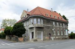 Wohnhaus / Geschäftsgebäude an  der Straße Stefana Żeromskiego in der polnischen Stadt Langenbielau/Bielawa; graue Putzfassade und runder Eckerker im ersten Geschoss.