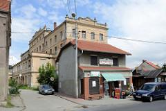 Kleine Geschäftshäuser  in der Hauptstraße Tadeusza Kościuszki von Pieszyce / Peterswaldau. Dahinter die Industriearchitektur eines leer stehenden Fabrikgebäudes.