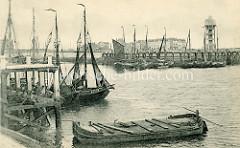 Historisches Bild vom Fischereihafen in Seebrügge; Fischerboote liegen am Ufer -im Vordergrund ein Kahn wahrscheinlich zur Aufbewahrung des Fischfangs.