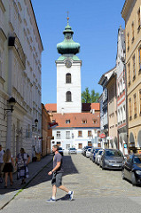 Blick durch die Straße Piaristicka zum Weissen Turm des Dominikanerklosters in Budweis. Der weiße Turm war Teil der Stadtbefestigung und wurde Mitte des 15.Jahrhunderts erbaut - 1772 wurde die Kupferkuppel im Rokkokostil aufgesetzt.