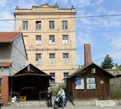 Kleine Geschäftshäuser aus Holz in der Hauptstraße Tadeusza Kościuszki von Pieszyce / Peterswaldau. Dahinter die Industriearchitektur eines leer stehenden Fabrikgebäudes.