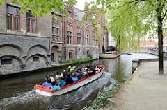 Ein mit Touristen vollbesetztes Motorboot fährt auf einer Gracht durch das historische Zentrum von Brügge; lks. die Fassade vom Kartuizerinnenklooster.