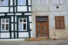 Alt + Neu, restauriertes Fachwerkgebäude mit grün gestrichenen Fachwerkbalken neben einem leerstehenden Wohnhaus mit Holztür, Holzluken  und Rauhputz.