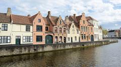 Blick über den Kanal Langen Kai zu historischen Wohnhäusern im typischen flämischen Architekturstil mit Treppengiebeln an der Straße Potterierei in Brügge .