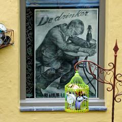 Altes Plakat - De drinker, betrunkener Mann mit Bierglas / Bierflasche betrunken an einem Tisch - Käfig mit alten Weckern, Uhren; Vorgarten an einer Gracht in Brügge.