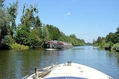 Schiffsverkehr auf dem Havelkanal bei Wustermark - Binnenschiff und Sportboot begegnen sich auf dem Wasser.