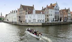 Wohnhäuser in unterschiedlichen Baustilen an der Straße Spiegelrei - auf der gleichnamigen Gracht fährt ein Boot mit Touristen auf deren Sightseeing-Tour. Im Hintergrund  ist der Turm der Poortersloge zu erkennen.