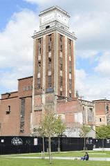 Grünanlage im Hafengebiet von Löwen/Leuven, Blick zur Ruine eines Silos - historische Industriearchitektur.