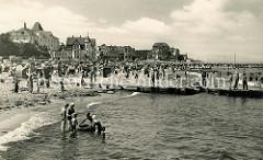Alte Fotografie vom Badestrand in Kühlungsborn an der Ostsee, Badegäste mit Kindern spielen im Wasser - am Strand stehen Strandkörbe in Sandburgen. An der Promenade des Ostseebades Hotels und Villen.