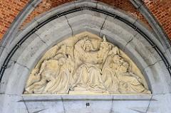 Relief im Tympanon des Zentralgefängnisses in Löwen / Leuven; Justitia mit Schwert und Waage - strafende Engelfigur mit Dolch und räuige SünderIn im Arm der Kirche.