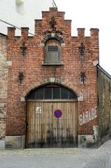 Altes Garagengebäude, Backsteingebäude mit Treppengiebel - Holztor und Dachluke, Schriftzug Garage; Architekturbilder aus der Stadt Brügge.