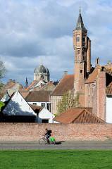 Backsteingebäude mit Treppengiebel und Turm an der Straße Carmersstraat / Kruisvest in der Stadt Brügge. Im Hintergrund die Kuppel vom English Convent.