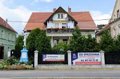 Alte Villa mit geschnitztem Giebel und Werbung am Gartenzaun in der Straße Wolności in Langenbielau, Bielawa. Links ein Flurkreuz - Kreuzigungsszene mit Christus mit türkisfarbigen Sockel.