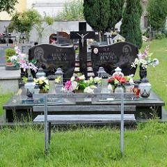 Friedhof mit bildgeschmückten Grabsteinen, Bildnisse von Maria und Jesus, Grabschmuck mit Plastikblumen - davor eine Holzbank; Kirchhof    an der Sankt Jakobskirche in Pieszyce / Peterswaldau.