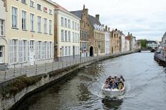 Wohnhäuser in unterschiedlichen Baustilen an der Straße Sint Annarei  - auf der gleichnamigen Gracht fährt ein Boot mit Touristen durch die Altstadt von Brügge.