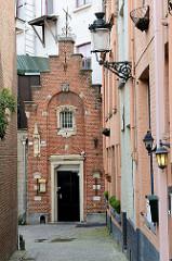 Wandlaternen und schmales Backsteingebäude mit Treppengiebel und Maria Skulpturen der Hauswand / Ave Maria in der Hoogste van Brugge.