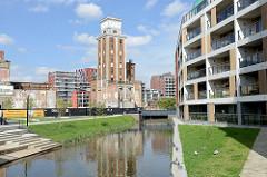 Neubauten/Wohnhäuser am kanalisierten Fluss Dijle in Löwen/Leuten, im Hintergrund   die Ruine  eines Silogebäudes am Hafen der Stadt.