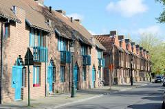Neubauten mit türkisfarbige Balkons und Fenstern in der Straße Kazernevest von Brügge - Wohnhäuser am Kanal.