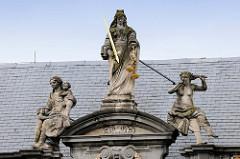 Skulptur / Figur der Justitia mit verbundenen Augen, Schwert und Waagschale - lks. vorbildliche Mutter mit Kindern, re. liederliches Weib; Giebel der Alten Probstei beim Burgplatz in Brügge. Errichtet 1666 als Bischöfliche Residenz.
