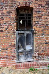Kleine, schief hängende Holztür mit vergittertem Oberlicht - Ziegelmauer; Fotos aus der Hansestadt Havelberg.